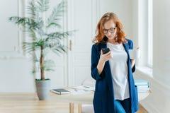 El tiro del empresario de sexo femenino serio enfocado en teléfono móvil, hace el pago vía el uso de las actividades bancarias, b fotos de archivo