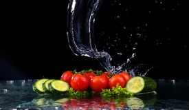 El tiro del estudio con el movimiento del helada de los tomates de cereza y las rebanadas de pepino en agua salpican en fondo neg Imagen de archivo