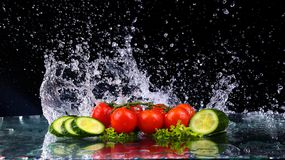 El tiro del estudio con el movimiento del helada de los tomates de cereza y las rebanadas de pepino en agua salpican en fondo neg Imágenes de archivo libres de regalías