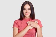El tiro del estudio de la mujer joven hearted buena de mirada agradable guarda las manos en pecho, expresa la gratitud, vestida e fotografía de archivo libre de regalías