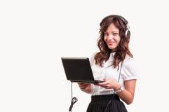 El tiro del estudio, de una empresaria que trabaja en el ordenador portátil y escucha Fotos de archivo libres de regalías