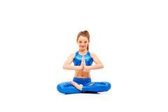 El tiro del estudio de una muchacha joven del ajuste que hace yoga ejercita en el fondo blanco Foto de archivo libre de regalías