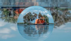 El tiro del paisaje contiene una cabaña en el medio del lago con la reflexión en la bola de cristal imágenes de archivo libres de regalías