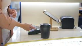 El tiro del primer de la mano del ` s del hombre hace el café para llevar para un cliente que pague por el teléfono móvil sin con almacen de metraje de vídeo