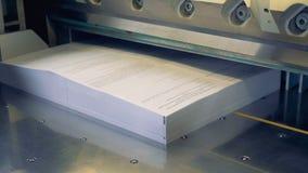 El tiro del primer de un trabajador puso el papel en la máquina industrial del corte de papel 4K metrajes