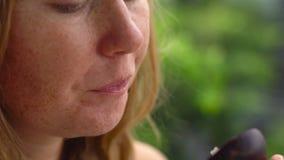 El tiro del primer de una mujer pelirroja come el mangostán jugoso fresco almacen de video