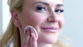 El tiro del primer del gris feliz observa a la mujer rubia que hace retiro del maquillaje usando el cojín de algodón almacen de metraje de vídeo