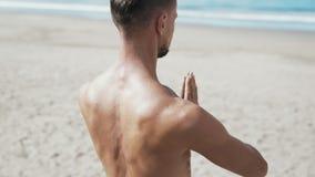 El tiro del steadicam de la cámara lenta del primer, hombre atlético que hacía la yoga en la playa con sus manos junta y los ojos metrajes