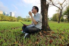 El tiro granangular del hombre joven alegre está riendo con un ordenador portátil en parque de la ciudad Fotografía de archivo libre de regalías