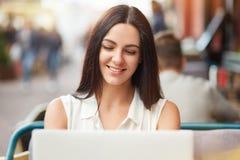 El tiro horizontal de la hembra caucásica joven hermosa se sienta delante del ordenador portátil abierto, sonríe suavemente, los  fotografía de archivo