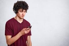 El tiro horizontal del hombre hermoso joven, tiene el pelo rizado oscuro, el individuo con el teléfono celular a disposición y au imagen de archivo libre de regalías