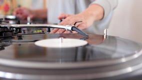El tiro lateral de un mezclador audio y de un vinilo que giran, DJ está mezclando música en casa, DJ está rasguñando en el vinilo almacen de video