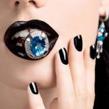 El tiro macro de los labios y de los clavos de una mujer pintó el blac brillante del color Imagen de archivo