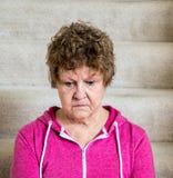 El tiro medio del centro envejeció a la mujer caucásica que parecía hacia abajo mientras que se sentaba en las escaleras alfombra fotografía de archivo libre de regalías