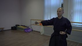 El tiro medio, el kendo principal tira de la espada katan del ` s de la envoltura y de los palillos él en envoltura almacen de video