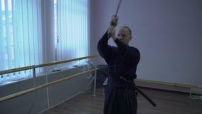 El tiro medio, samurai en kimono hace el kata con la espada del catana metrajes