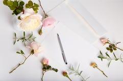 El tiro plano de la endecha de la letra y del sobre blanco en el fondo blanco con inglés rosado subió Tarjetas de la invitación o Fotos de archivo libres de regalías