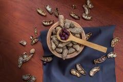 El tiro a?reo del cuenco del cacahuete con la c?scara, algo se pela al lado de una cuchara de madera imagen de archivo libre de regalías