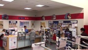 El tiro superior de la gente se alinea para tomar el paquete en la oficina de correos