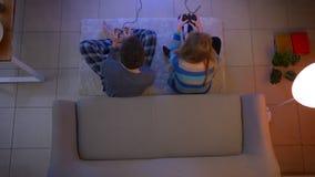 El tiro superior de pares en la ropa de noche que juega el videojuego con las palancas de mando en el piso da cinco feliz en la s almacen de metraje de vídeo
