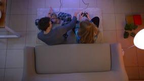 El tiro superior de pares en ropa de noche juega el videojuego con las palancas de mando que se molestan en el piso en la sala de almacen de video