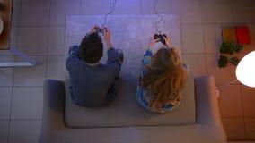 El tiro superior de pares jovenes en la ropa de noche que juega el videojuego con las palancas de mando gana y da cinco feliz en  almacen de video