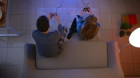 El tiro superior de pares jovenes en la ropa de noche que juega el videojuego con triunfos y el individuo de la muchacha de las p almacen de video