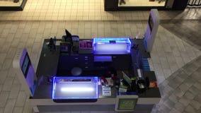 El tiro superior del trabajador elabora la tienda del closing dentro del minorista del boleto de lotería de la alameda