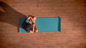 El tiro superior, hombre fuerte se está sentando en la estera de la yoga en la posición de la meditación y está llevando a cabo s metrajes