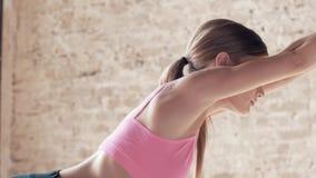 El tiroteo a cámara lenta ejercita el primer de la yoga Muchacha deportiva que hace ejercicios en compañero El estirar y estabili almacen de video
