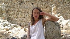 El tiroteo circular, la muchacha se sienta en la albañilería en el castillo almacen de metraje de vídeo