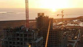 El tiroteo de un abej?n debajo del edificio de varios pisos de la construcci?n contra la puesta del sol, los constructores camina imagenes de archivo