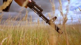 El tiroteo del primer, manos del soldado en camuflaje está sosteniendo el arma del arma automático, mientras que el viento está s metrajes