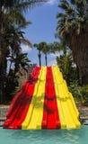 El tobogán acuático rojo y amarillo colorido en aguamarina parquea Imagenes de archivo