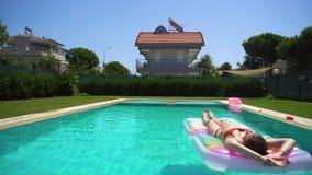 El tomar de la mujer toma el sol la mentira en el flotador de la piscina metrajes