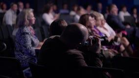 El tomar del hombre de la cámara fotos en la rueda de prensa