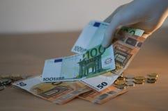 El tomar/robo del dinero de la tabla fotos de archivo
