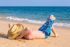 El tomar el sol turístico joven en la playa con el mar Foto de archivo