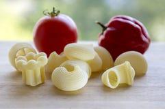 El tomate rojo, rojo del habanero madurado y la diversa mezcla de pastas en la tabla de madera, alistan para cocinar, cocina ital Fotos de archivo libres de regalías