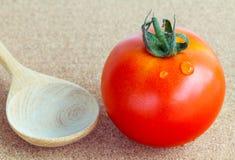 El tomate rojo gigante con la cuchara de madera Imagen de archivo
