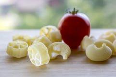 El tomate rojo y la diversa mezcla de pastas en la tabla de madera, alistan para cocinar, cocina italiana Foto de archivo
