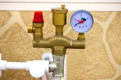 El tonelero del ` s del sistema de calefacción instala tubos con las vávulas y el manómetro de bola en una pared gris fotografía de archivo