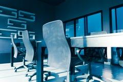 El tono azul de la mesa de reuniones y las sillas con el sol se encienden en la reunión Foto de archivo