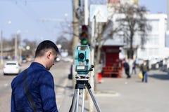 El topógrafo de la tierra del ingeniero hace medidas en la calle de la ciudad de Chernigov, Ucrania imágenes de archivo libres de regalías