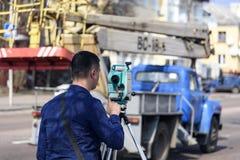 El topógrafo de la tierra del ingeniero hace medidas en la calle de la ciudad de Chernigov, Ucrania foto de archivo