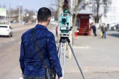 El topógrafo de la tierra del ingeniero hace medidas en la calle de la ciudad de Chernigov, Ucrania fotografía de archivo