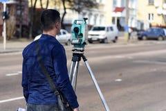 El topógrafo de la tierra del ingeniero hace medidas en la calle de la ciudad de Chernigov, Ucrania, abril de 2018 imagen de archivo libre de regalías