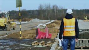 El topógrafo del inspector está mirando el proceso de la construcción de carreteras antes de poner del material de la capa de bal almacen de video