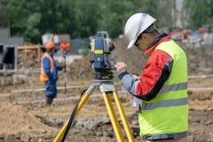 El topógrafo hace el taquímetro de las medidas e incorpora datos fotos de archivo