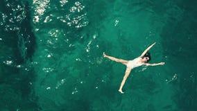 El top de la antena abajo tiró de una mujer joven hermosa en un traje de baño blanco que se bañaba en el mar Foto de archivo libre de regalías